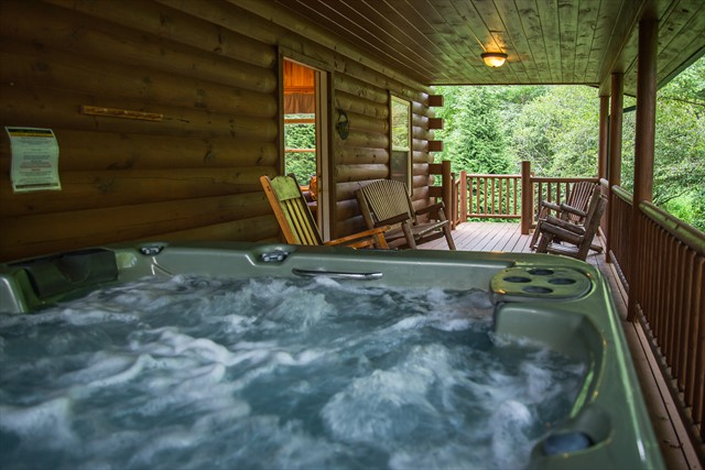 The covered porch features a hot tub