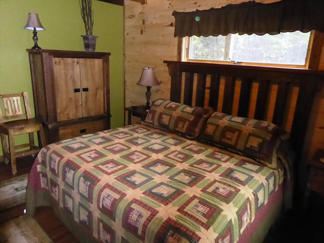 The bedroom features a king bed and a custom made barn board